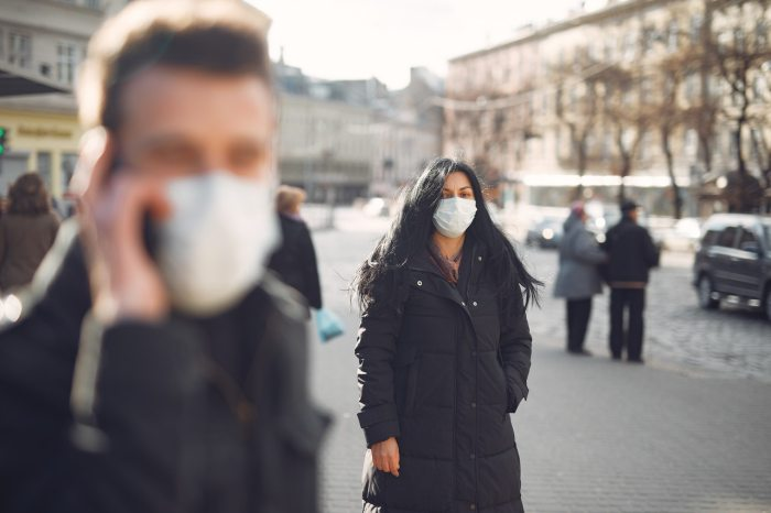 woman-in-black-coat-and-face-standing-on-street-3983428